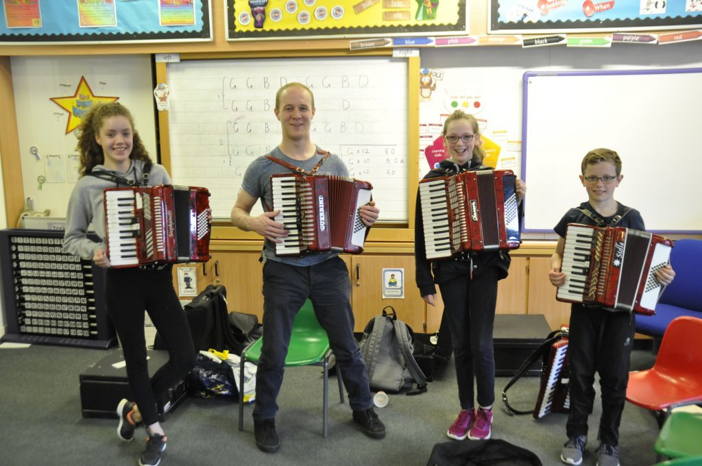 Murray Willis stands alongside his accordion playing students. 17_t15Feis04
