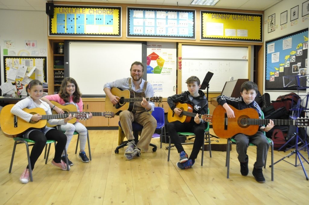 Tutor, Jamie Smith, and co get ready to play the guitar. 17_t15Feis07