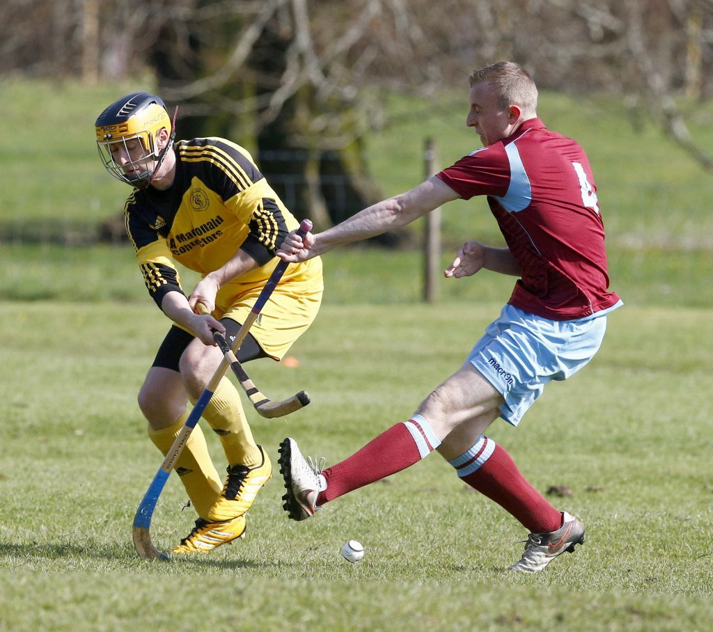 Law Jones of Strathglass gets his block in against Inveraray's Grant  Griffin during last weekend's National Division match at the Winterton which the away side won 2-1. Photograph: Stephen Lawson.