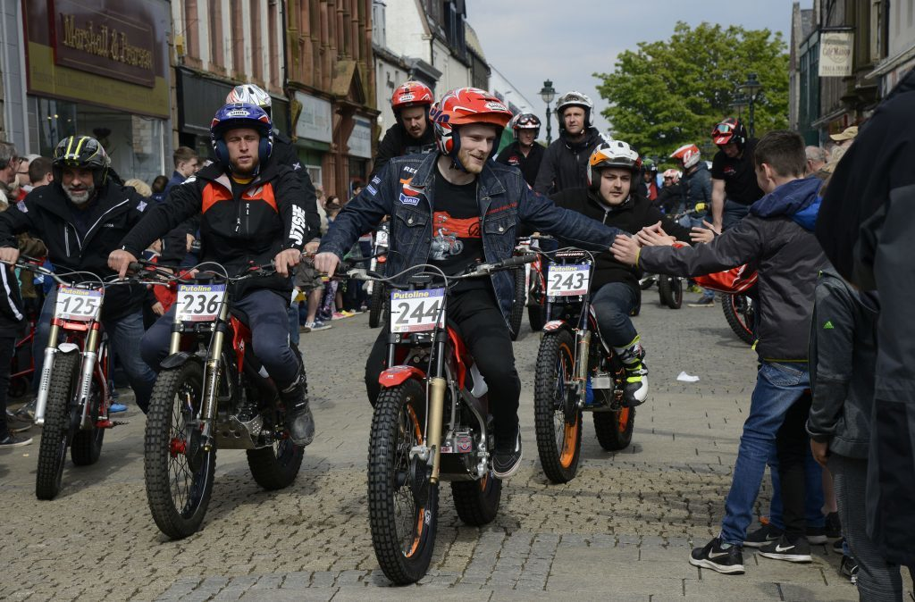 Children along the route of the parade share 'high fives' with Bolton riders, Jimmy and Adam McCanna. Photograph: Iain Ferguson, The Write Image