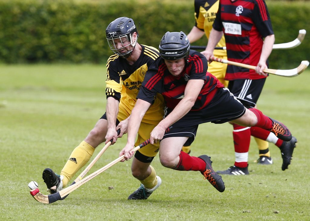 Oban Camanachd's Willie Neilson dives into a tackle with Inveraray's Nicholas Crawford. Photograph: Stephen Lawson.