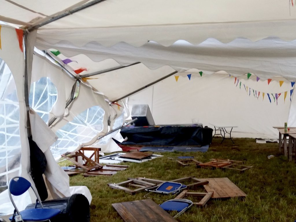 Damage caused by freak winds early Friday morning is clearly visible at the refreshments and food marquee