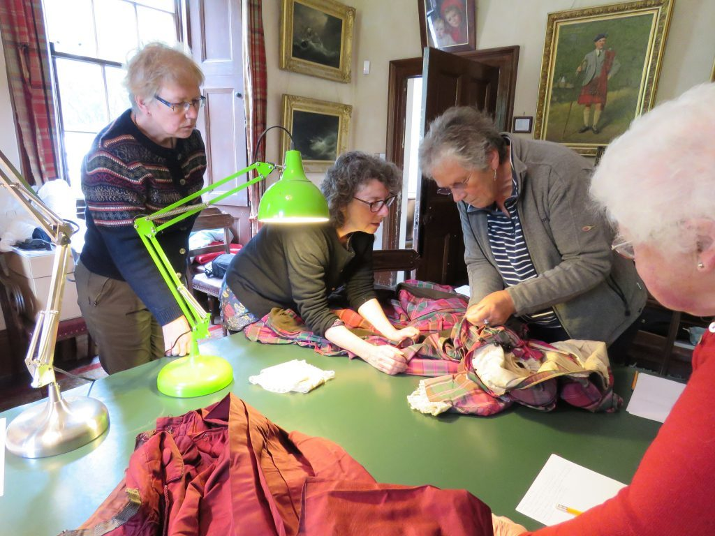 Dunollie's heritage director Catherine Gillies providing volunteers with training in handling ancient textiles.