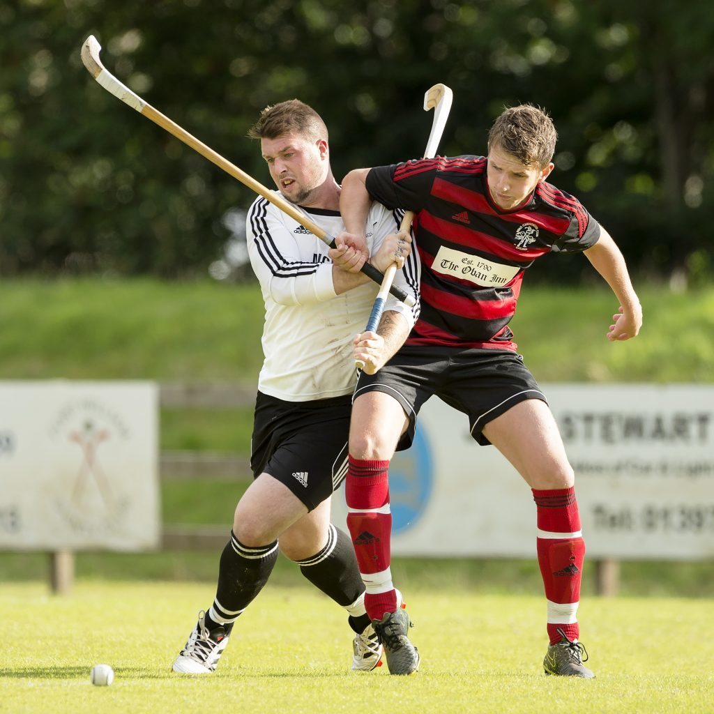 Marc MacLachlan, making his debut for Lovat, in a duel with Oban Camanachd's Gary McKerracher. Photograph: Neil Paterson.