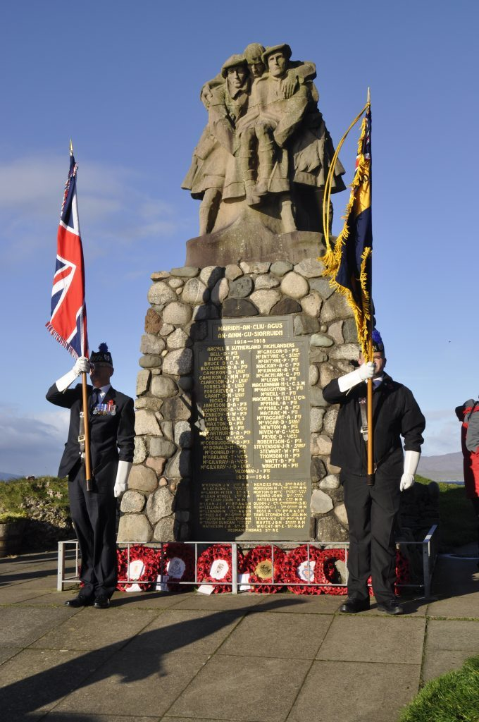 The flag bearers stand next to the War Memorial. 17_T46_RemembranceSunday10