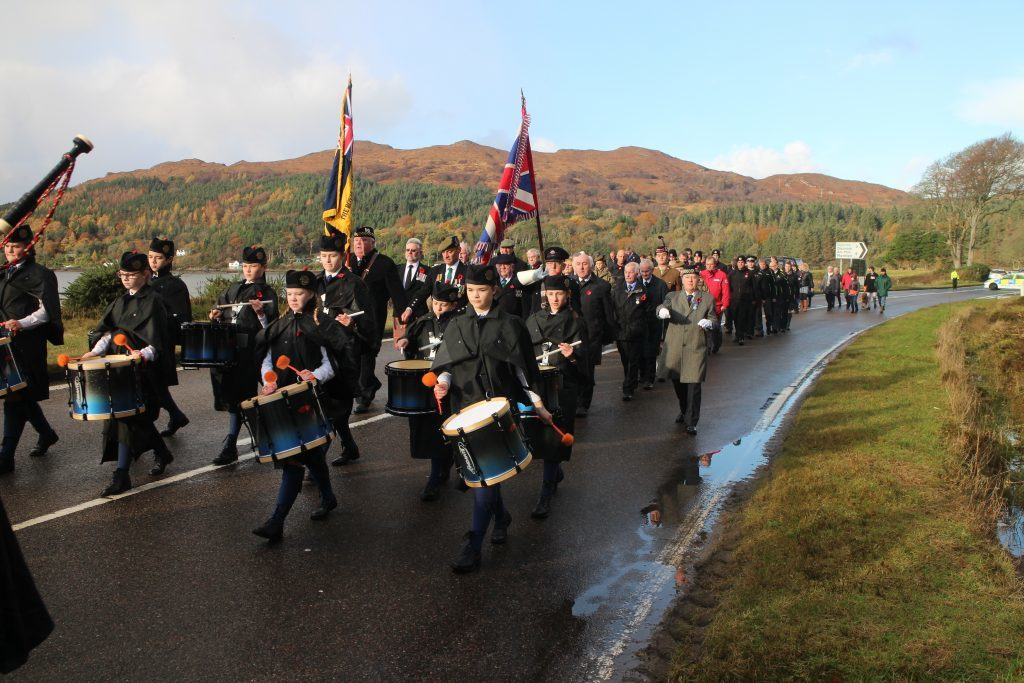 Lochalsh Junior Pipe Band led the procession along the road from Balmacara. NO F46 Remembrance Lochalsh 01.