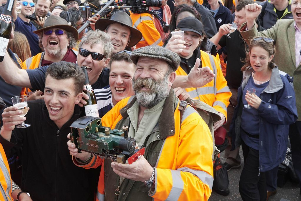 Presenter Dick Strawbridge holds the model engine, while volunteers celebrate the project's success.  Britain's Biggest Little Railway