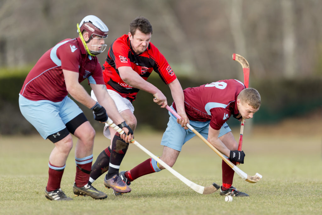 Glenurquhart's David MacLennan goes between Strathglass players Michael Stokes and Lewis Douglas. Photograph: Neil Paterson.