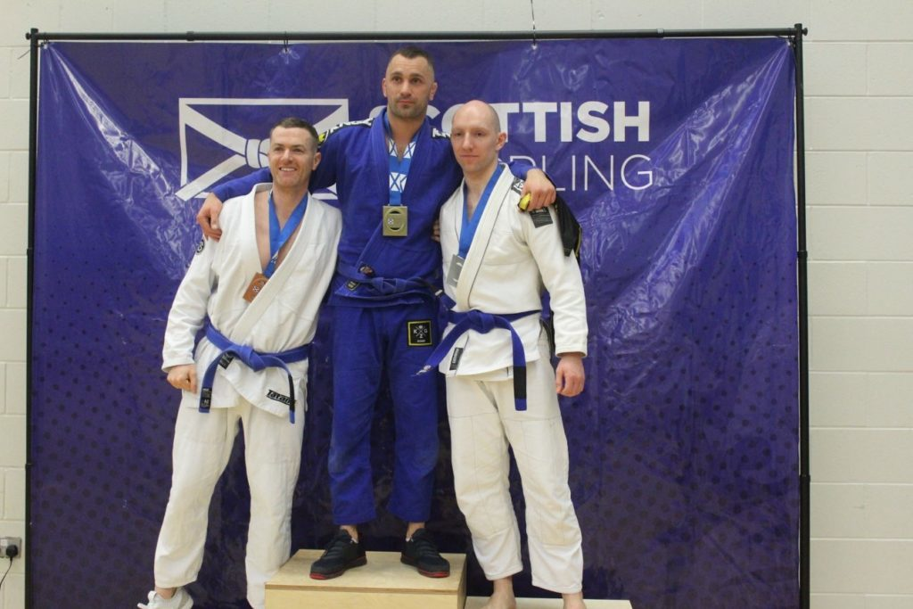Oban BJJ's Mateusz Grabiec, centre, picked up two gold medals at the West of Scotland winter cup tournament held at Ravenscraig recently.