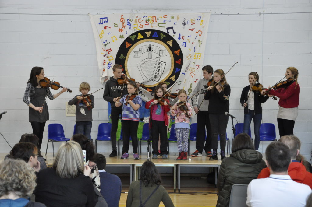 A group of fiddlers performed in front of a packed audience.  16_t15_Fèis14