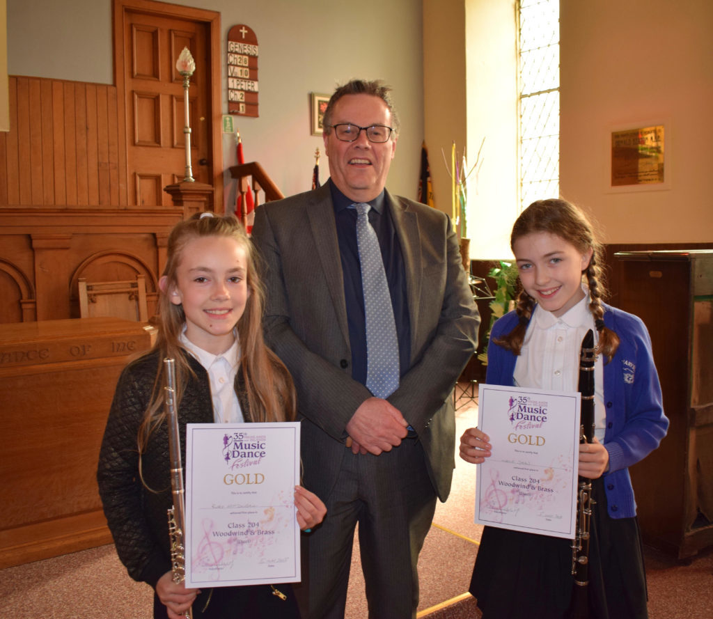 Ruby McDougall and Maisie Shaw from Taynuilt, win Gold in the woodwind duet section. Pictured with adjudicator Donald Finlayson NO-T19_winners01