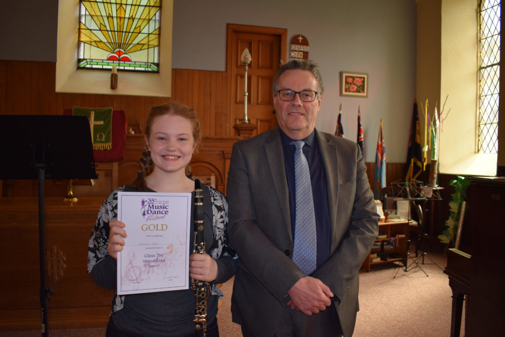 Smiles from Megan Day, Taynuilt won Gold in the Woodwind section (Secondary 1st Year) pictured with adjudicator Donald Finlayson NO-T19_winners02