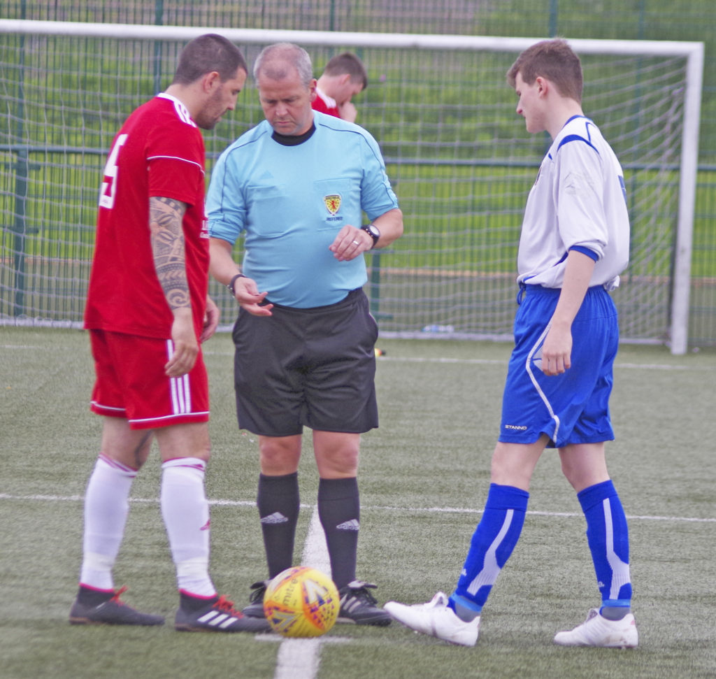 Team captains Donald Campbell and Gary Nicholson with referee John McQuilter at the coin toss.