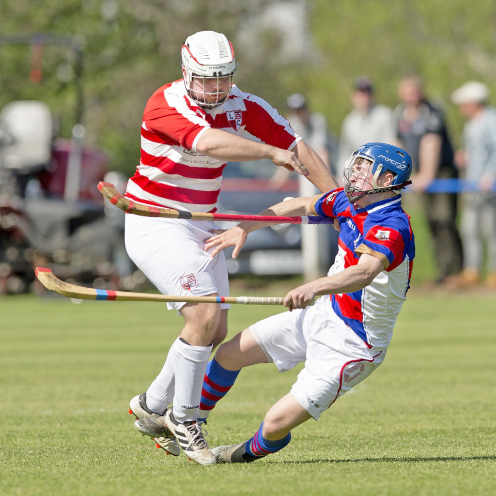 Kingussie's James Falconer comes off worst in this challenge with Lochaber's Danny Delaney. Photo: Neil Paterson