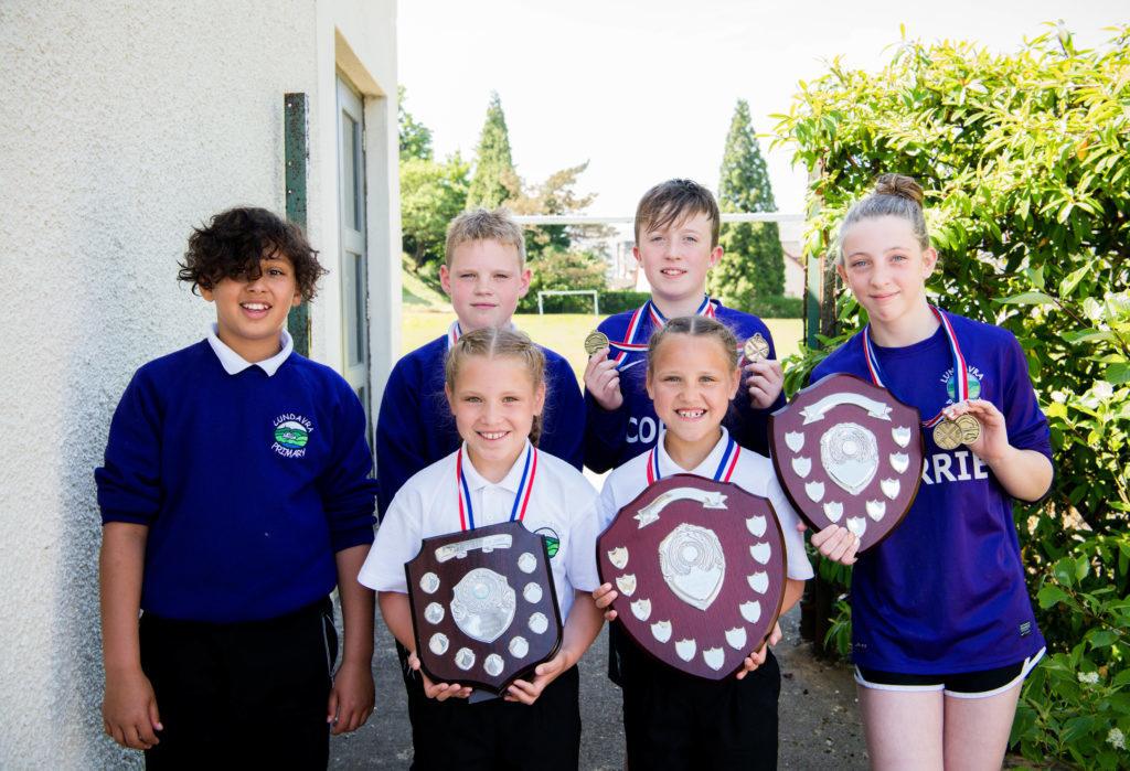 Lundavra Primary School with their trophy haul at the Inter-School sports day. JP F23 Inter Schools 08