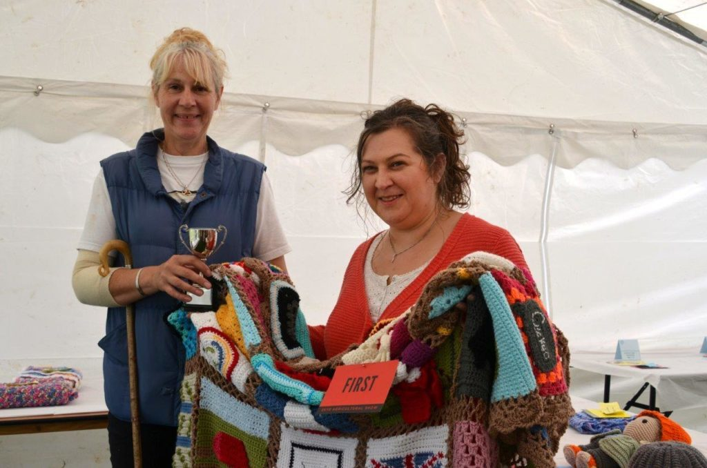 Jennifer MacInnes from Portree receives her trophy as overall winner of the knitting and crochet classes in the crafts section from judge Yasmin Milburn of Island at the Edge in Edinbane.