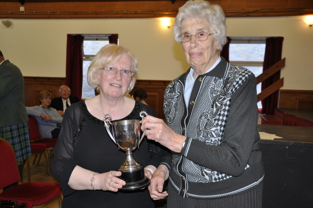 Morag Fraser hands over the Detta MacLean Memorial Trophy to Còisir Ghàidhlig an Eilein Mhuilich's conductor Elizabeth Jack. Mull won the choral ladies event. 17_T37_MullMod23