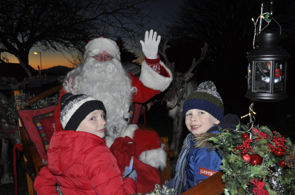 Santa with Rotary Christmas card competition winners Alexander Maxwell and Nathan Isaac, both six, in the sleigh at the start of the reindeer parade.