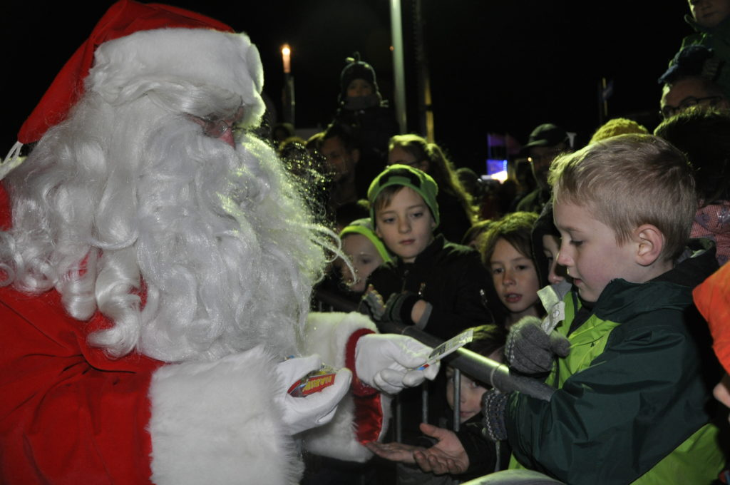 Santa stops off to hand out sweets to children in the crowd as the Christmas countdown begins.