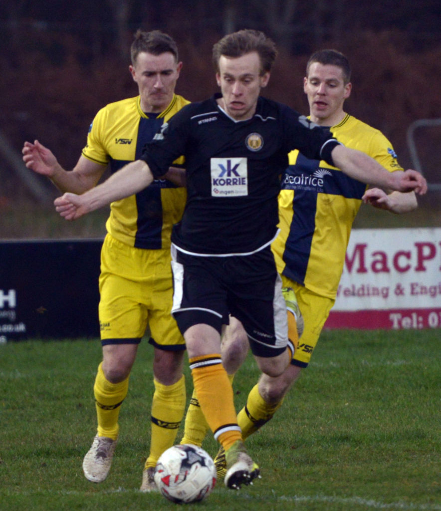 The Fort's Calum Browett skips past two defenders. NO F47 Fort Wick 02