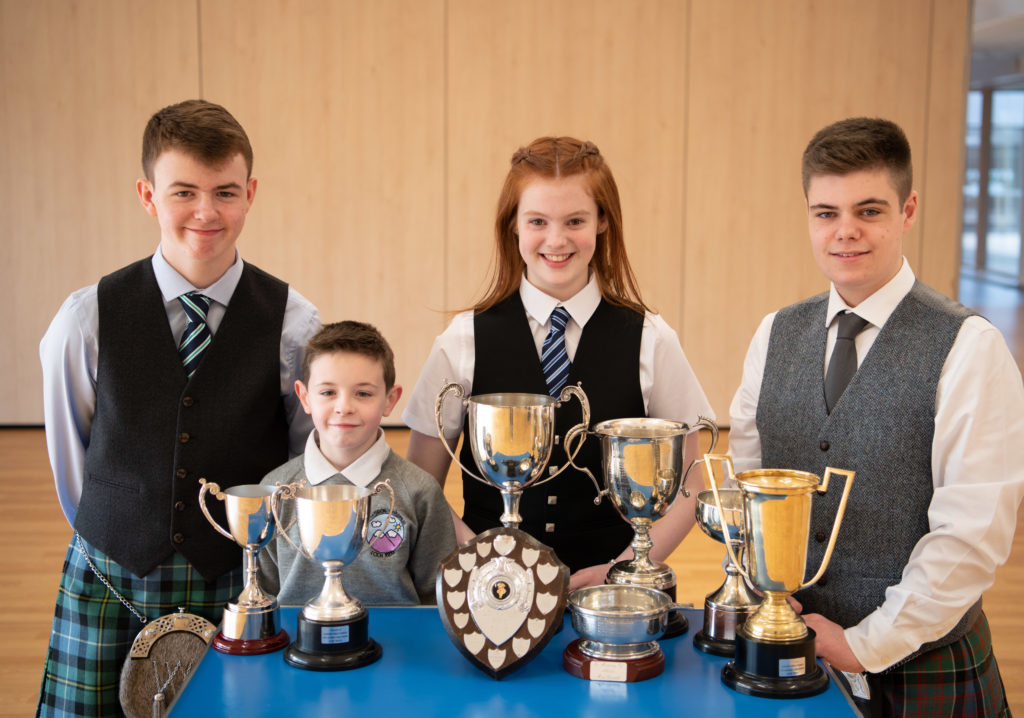 Lochaber pipers Ronnie McIntosh, Jamie Smith, Laura Robertson, and Andrew Orr with their trophy haul.