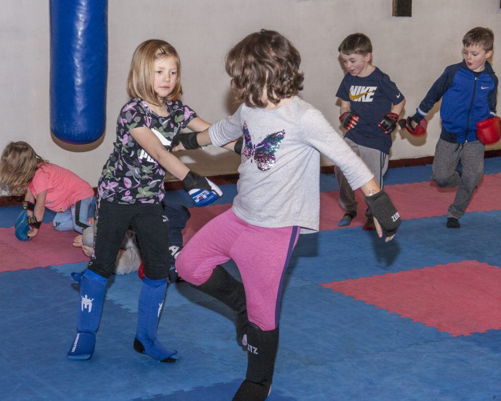 Erica Bales sparring with Eva Reeves with Aiden Steeman and Paul Gillespie in the background at the recent kickboxing grading.