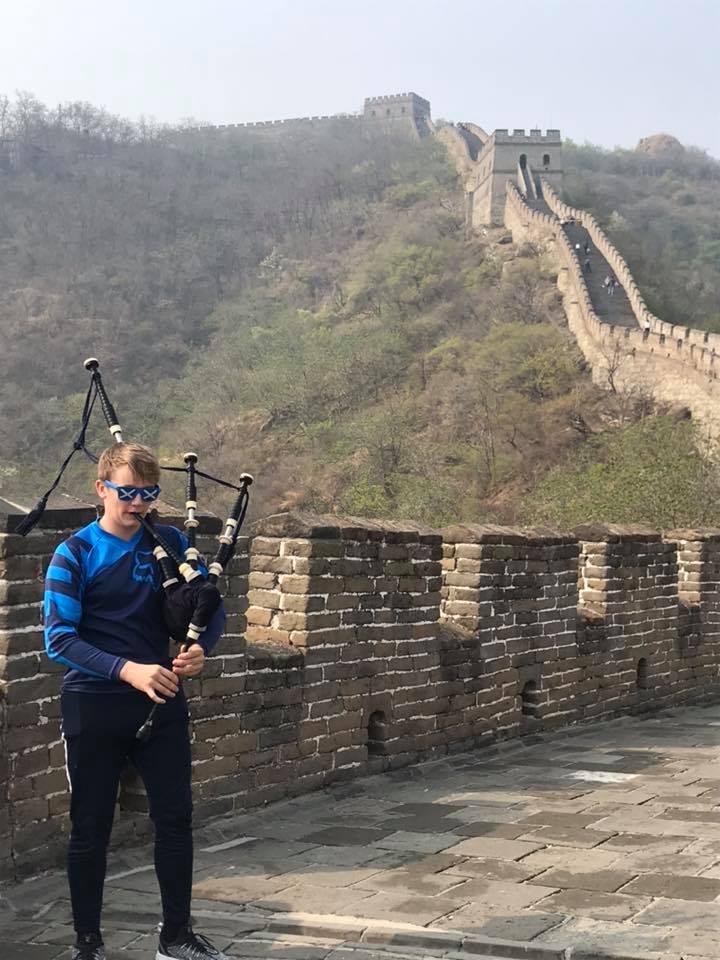 S2 pupil Struan Robertson plays his pipes on the Great Wall.  NO F18 Mallaig Music China 08
