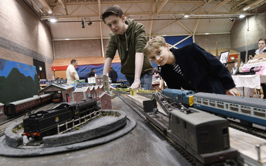 Shaye O'Hagan, 15, explains his representation of the old Fort William turntable and engine shed to keen railway enthusiast Findlay Hunter, 11. Shaye created the layout  especially for Saturday's show in the Nevis Centre.  Picture Iain Ferguson, alba.photos  NO F19 Model show 02