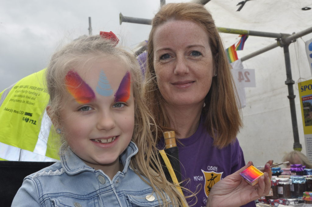 Annelie Murphy, 7, has her face painted by Lindsay MacLean from Oban High School's parent council.