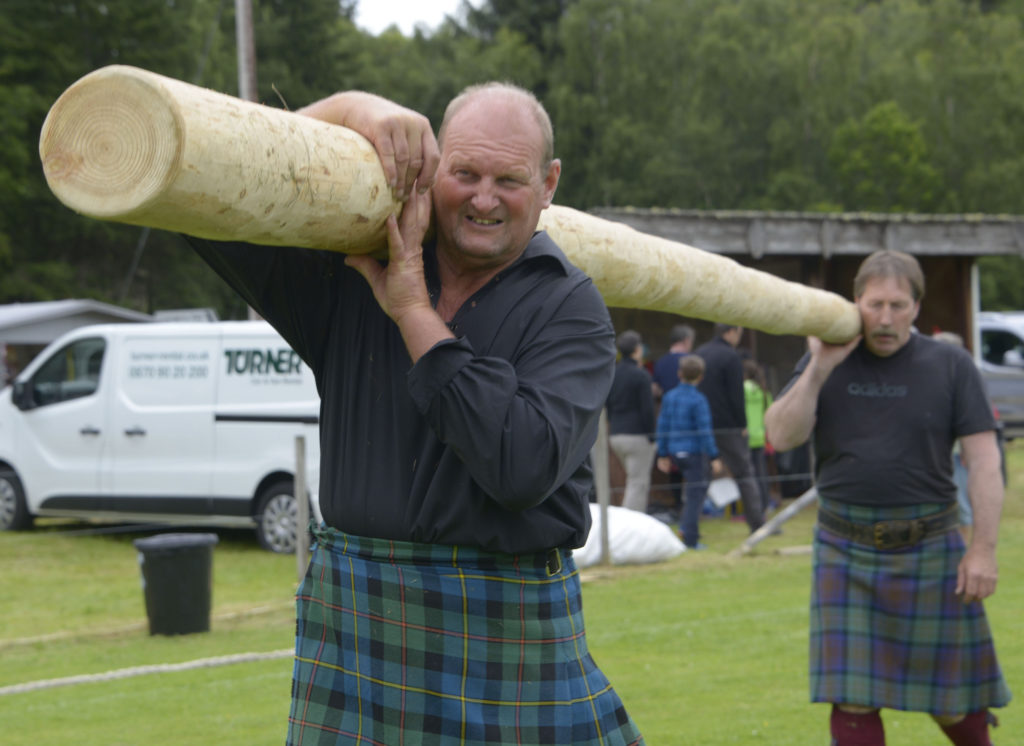 Heavy athletes William Simmons, left, and David MacDonnell, carry the caber to the start point before tossing it in the traditional Highland event. Photograph: Iain Ferguson, alba.photos
