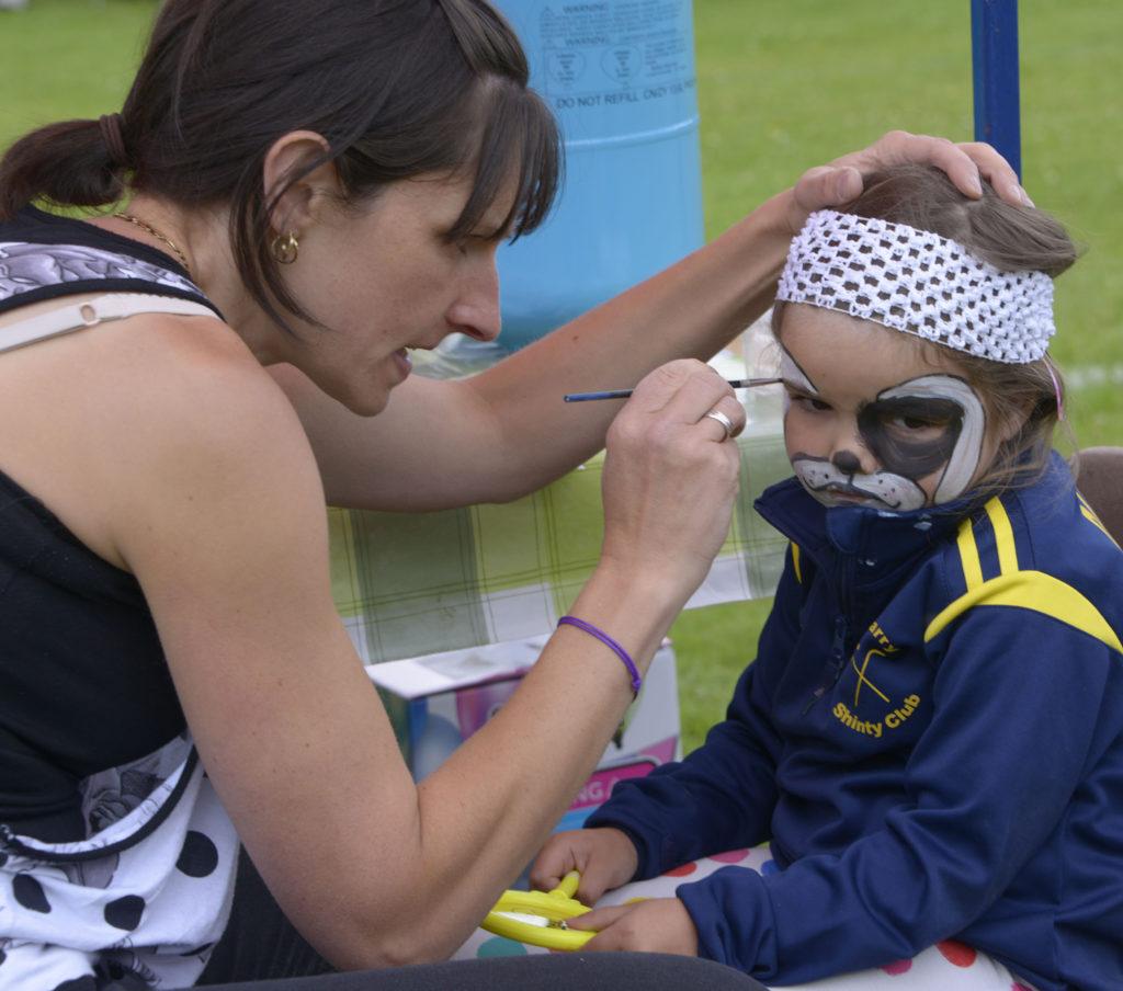 Karen Williamson paints daughter Darcy's face ain aid of Glengarry ladies shinty club. Photograph: Iain Ferguson, alba.photos