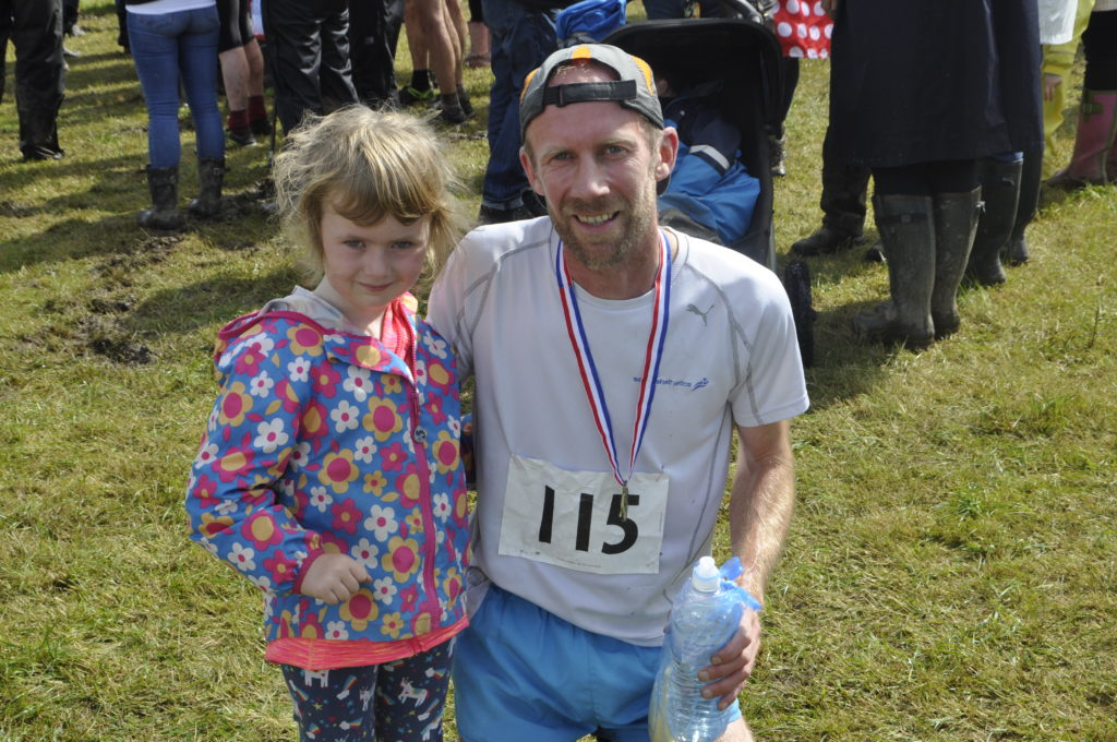 Lochaber AC athlete Tom Smith celebrates his hill race win with his daughter Polly.