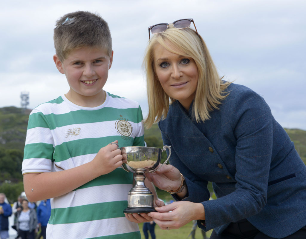 Games chieftain Kirsteen MacDonald presents the winner of the children's race with his trophy. Photograph: Iain Ferguson, alba.photos
