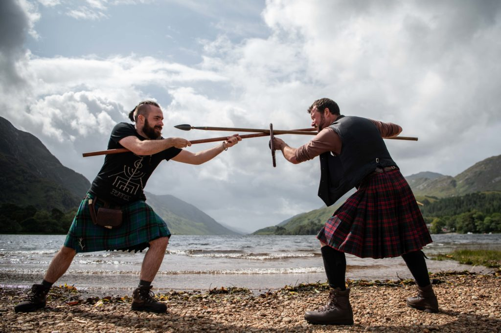 The waters of Loch Shiel provide an atmospheric backdrop to these two 'clansmen' displaying their weaponry skills.  NO F34 Glenfinnan games spears