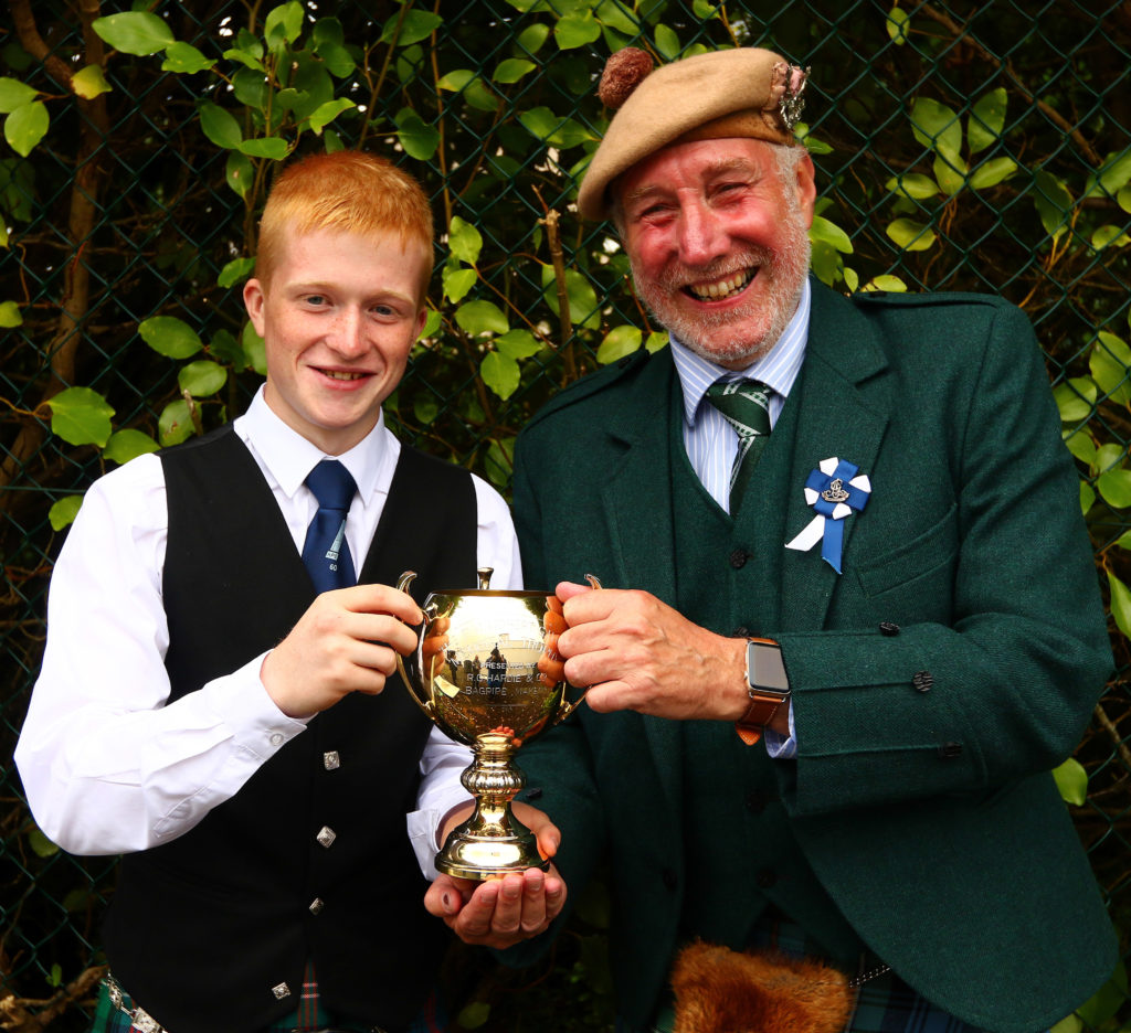Ross Conner, Campbeltown, is presented with the trophy for intermediate march, strathspey and reel by Torquil Telfer, piping steward.