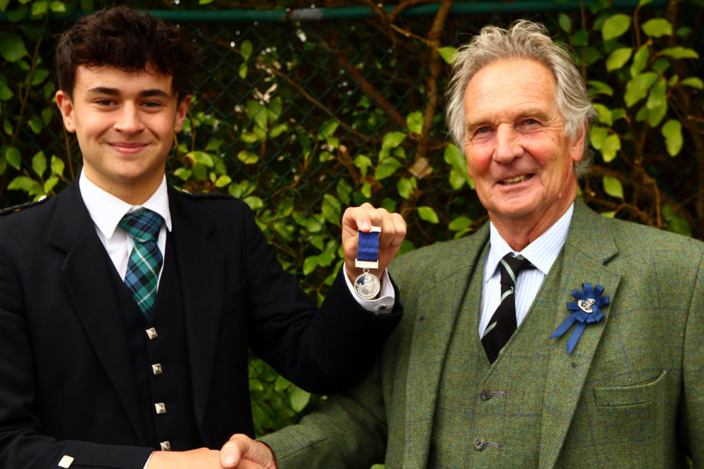 Ruaridh Brown won the U22 MacGregor Memorial Piobaireachd and was presented with his medal by piping steward Jamie Mellor.