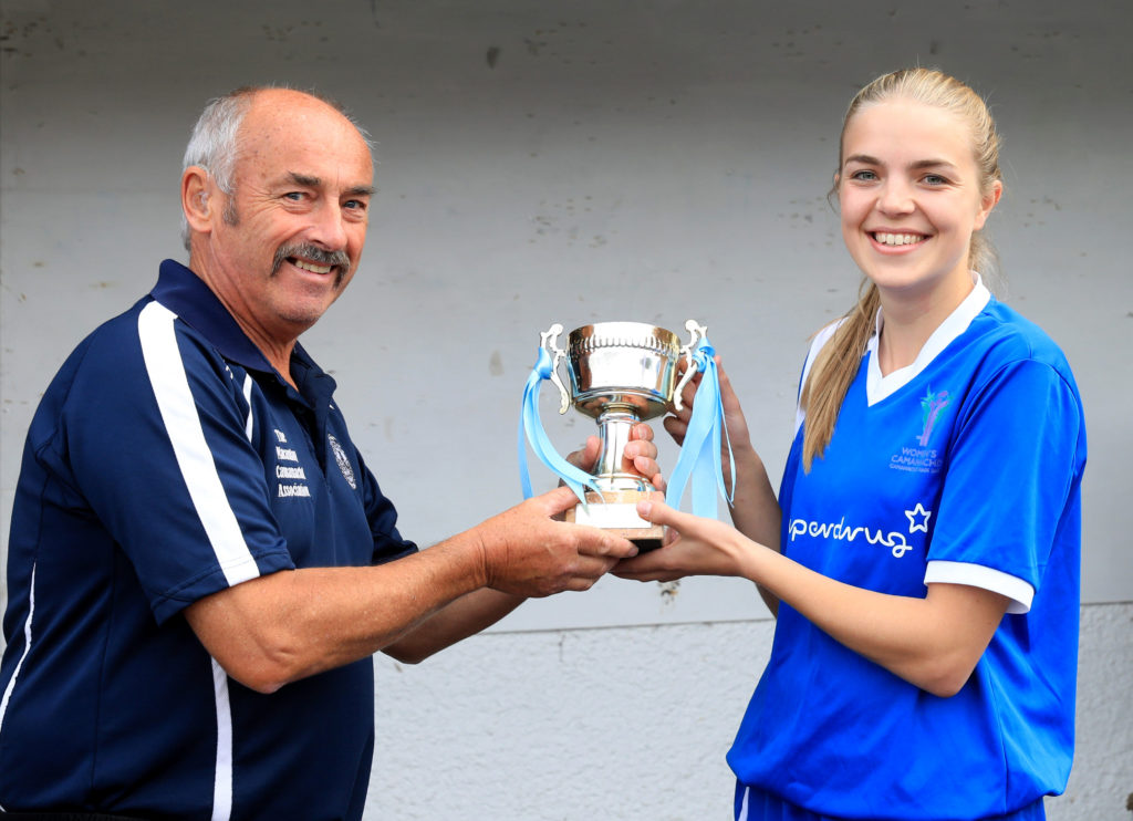 Blue Area senior team captain Rhona McIntyre receives the trophy from the Macaulay Association's David Hamilton.