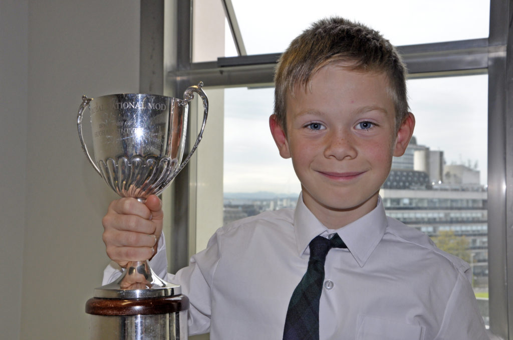 Robbie Donald MacLean, eight, from Barra's Sgoil Eolaigearraidh came top in solo singing eight years with Bata Alasdair, and lifted the Hugh MacIntyre Memorial Trophy in his first time at the national Mòd. 'I've been practising 15 times this morning, although it feels like 1,500 times,' he said. His teacher John James Galbraith would be 'surprised' he said, adding: 'He thought I would come second.' As a reward, his proud mum and school teacher Jennifer Campbell promised to take him sledging. 15_SN_ModMon_08