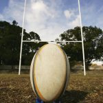 A rugby ball on a kicking tee in front the goal posts