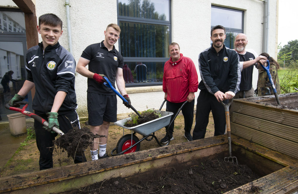 Football club lend green hands to school garden clean up